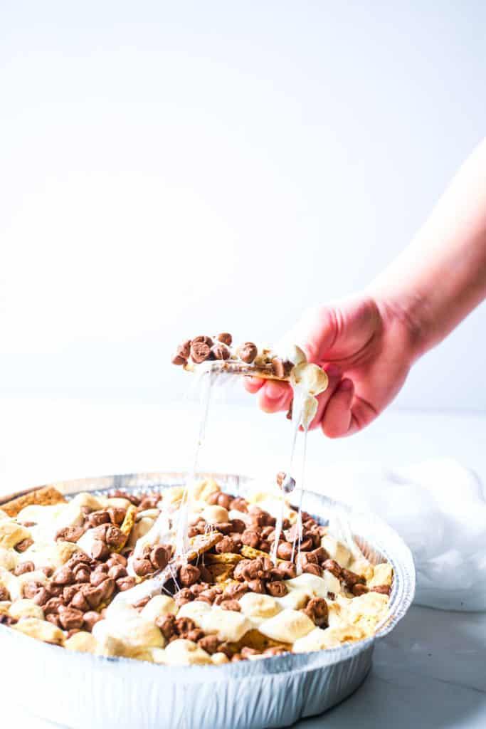 hand taking some smores nachos